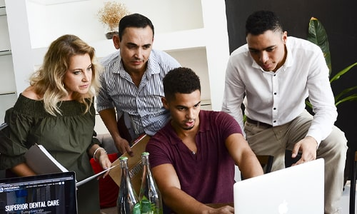 Four members of Roadside's team looking at a computer and discussing dental seo