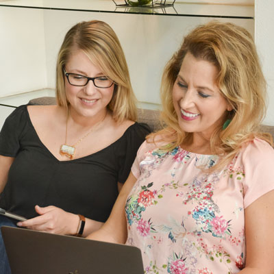 Shannon and Whitney looking at a computer and smiling