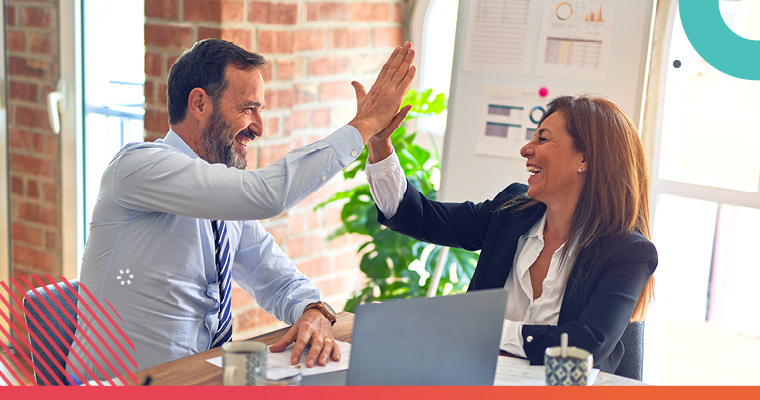 Two professionals high-fiving while in a business meeting